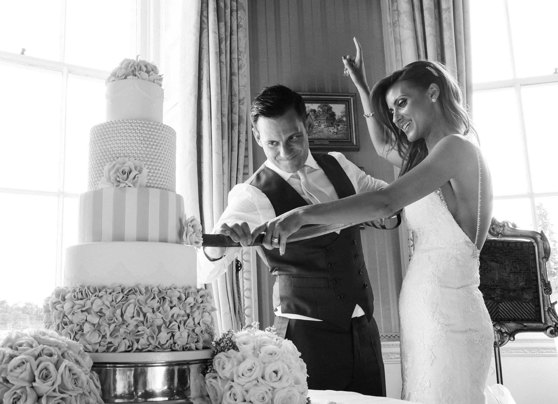 Coppia di sposi tagliano la torta nuziale con una sciabola antica