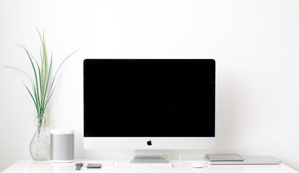 Scrivania con computer iMac e pianta